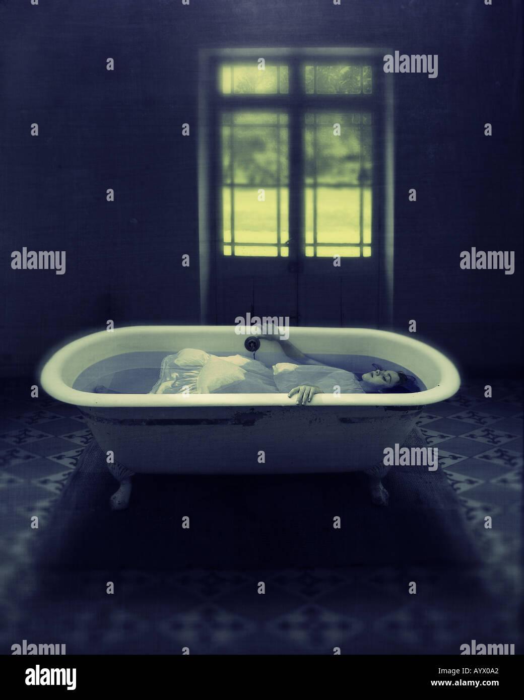girl in white dress immersed in water in bathtub in empty room with door to garden Stock Photo