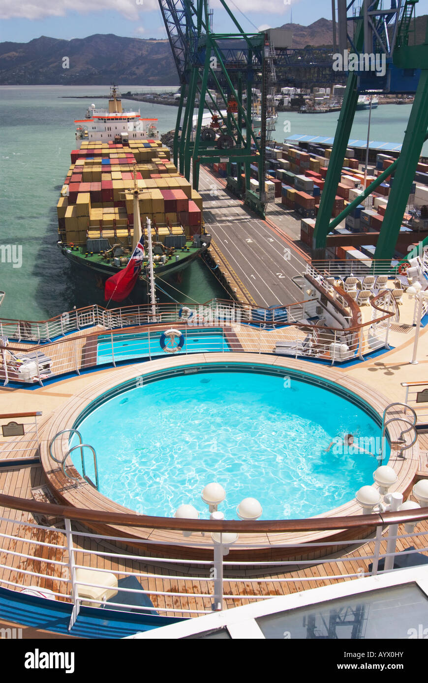 Aft decks of a cruise ship with swimming pool and a container ship berthed astern in Lyttelton, New Zealand Stock Photo