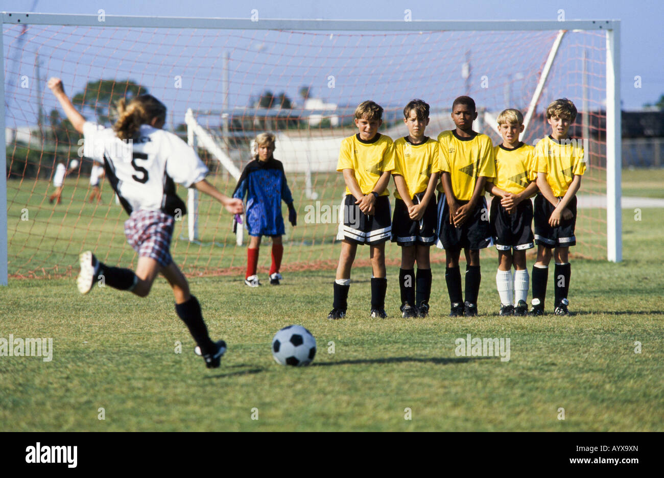 Kids soccer team, girls and boys together, with coach teaching skills, teamwork, teamspirit, Melbourne, Florida - Stock Image