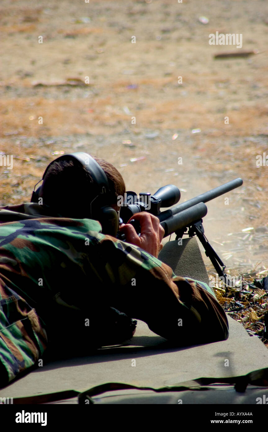 Rifleman in prone position firing sniper rifle on firing range - Stock Image