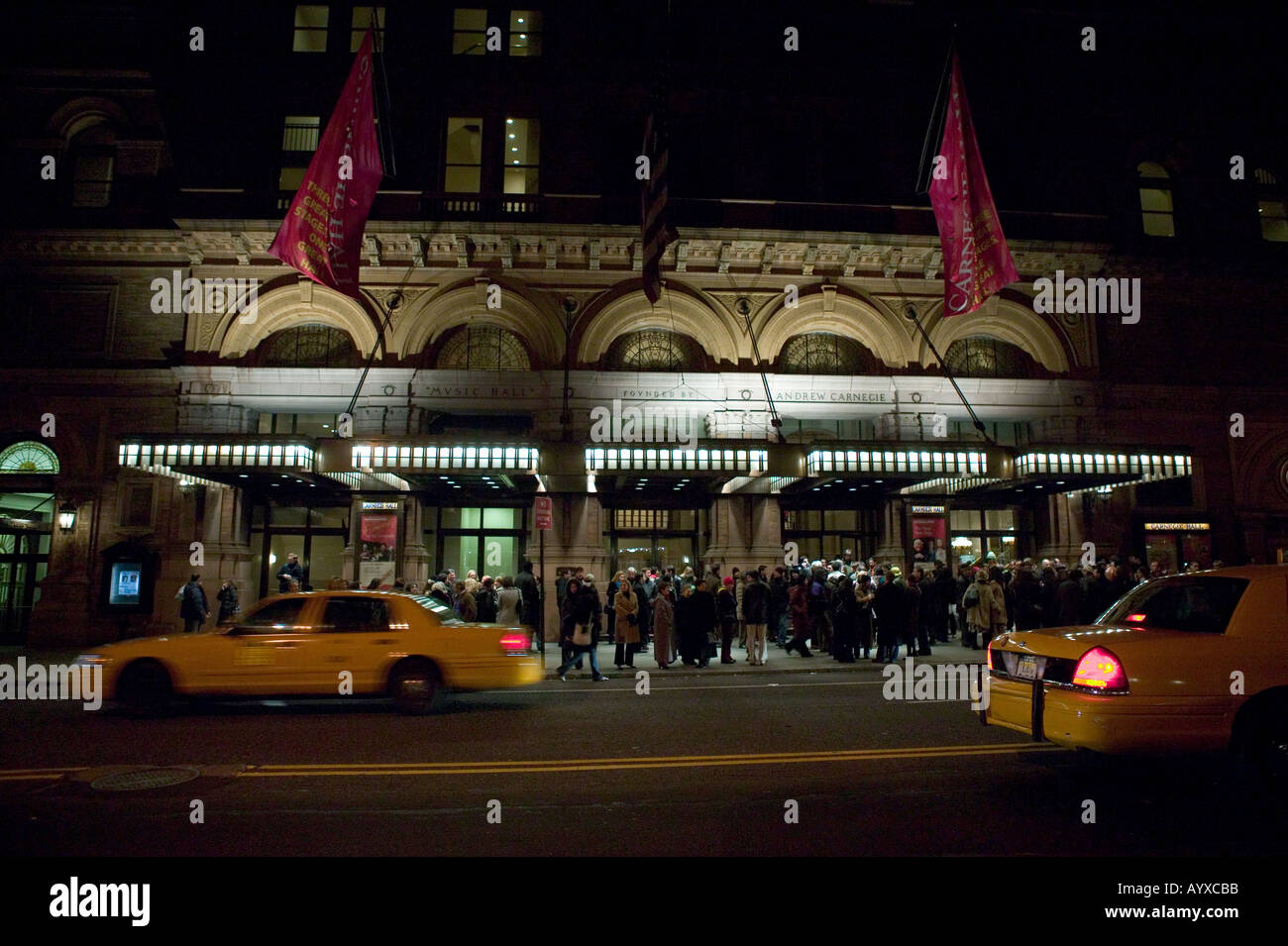 Yellow cabs drive past as spectators leave Carnegie Hall in New York USA after a show February 2005 - Stock Image
