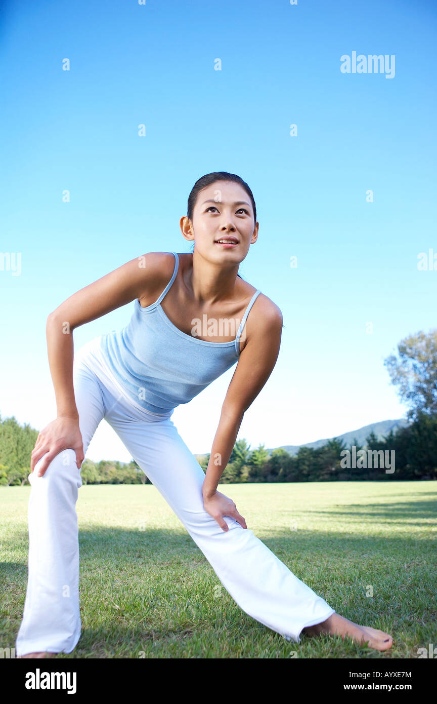 a woman excising on grass field - Stock Image