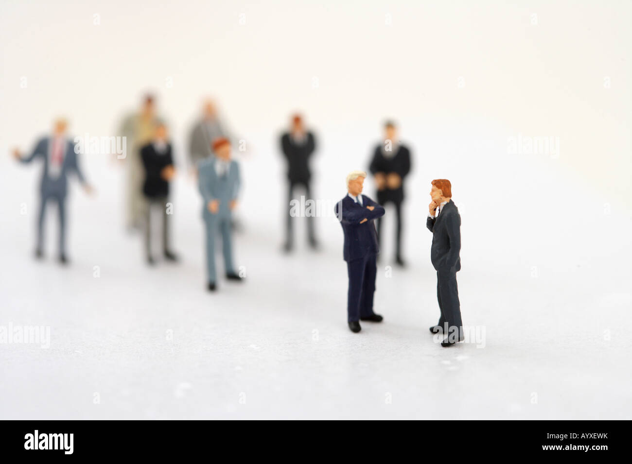 Two businessmen figurines talking, other ones in background - Stock Image