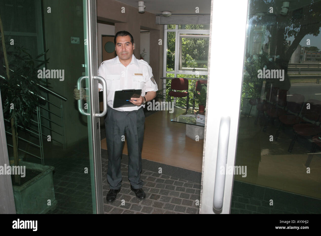 A Security Guard Opening The Front Door Of A Company Or ...