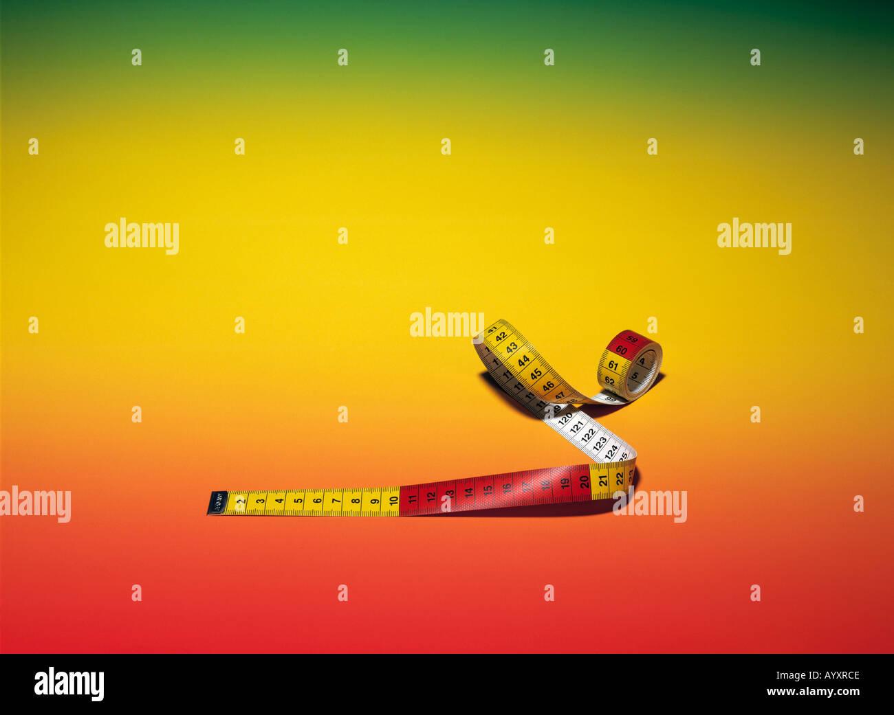 measuring tape, measure, background, coloured, studio photograph, symbolism, symbolical Stock Photo