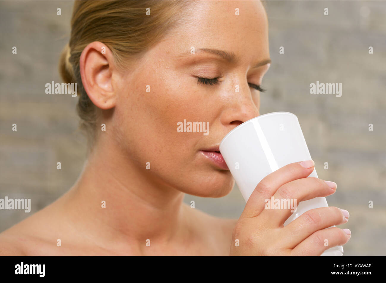 Young woman with closed eyes drinking of a glass - Stock Image