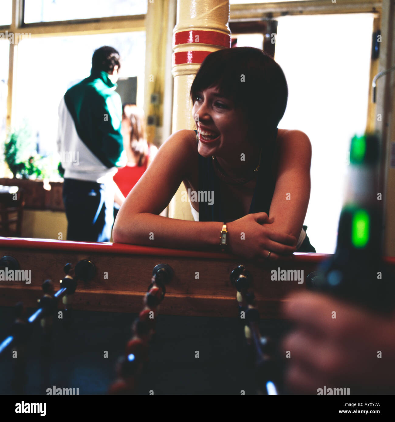 Girl playing table football in bar - Stock Image