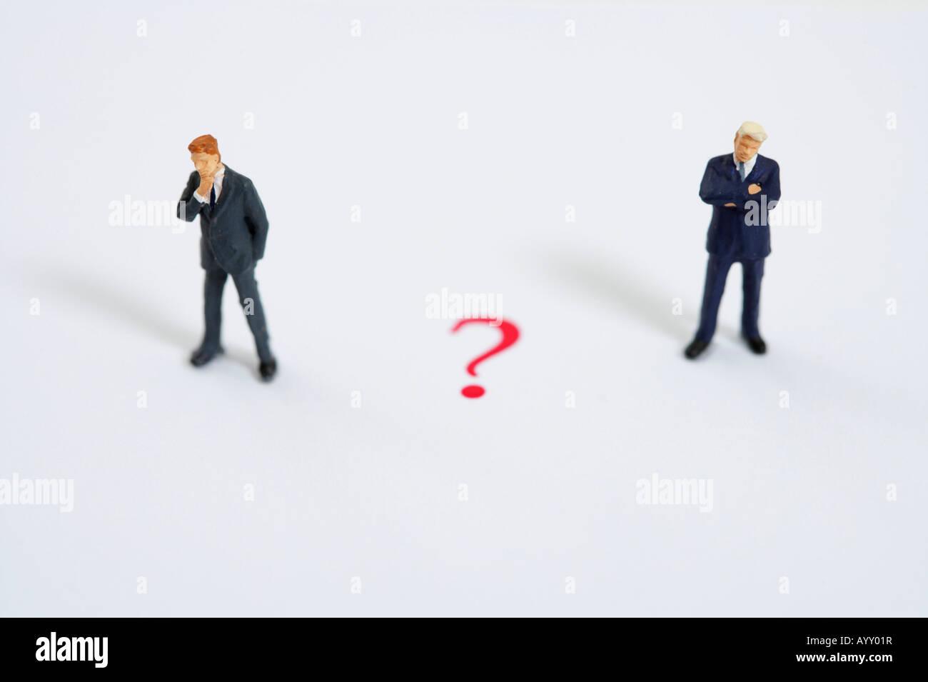 Question mark between businessmen figurines - Stock Image