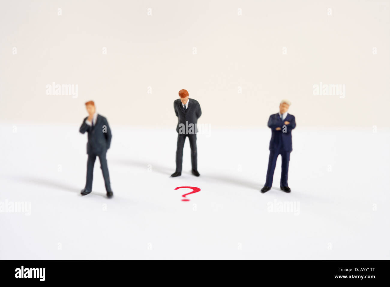 Three businessmen figurines and question mark Stock Photo