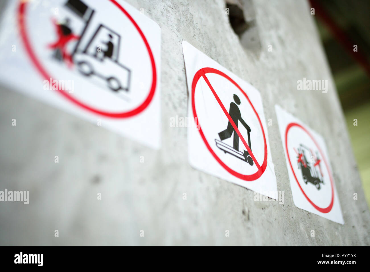 Prohibition signs on a concrete wall - Stock Image