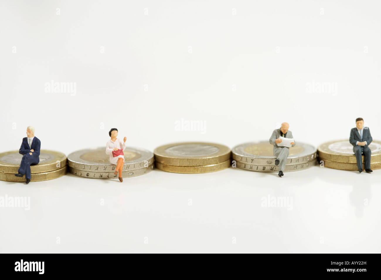 Businesspeople figurines sitting on coins - Stock Image