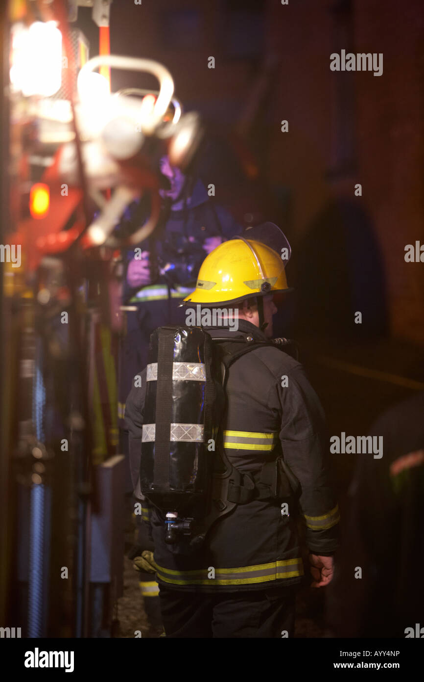 firefighter wearing breathing apparatus waits at the rear of a fire tender truck at the scene of a house fire in - Stock Image