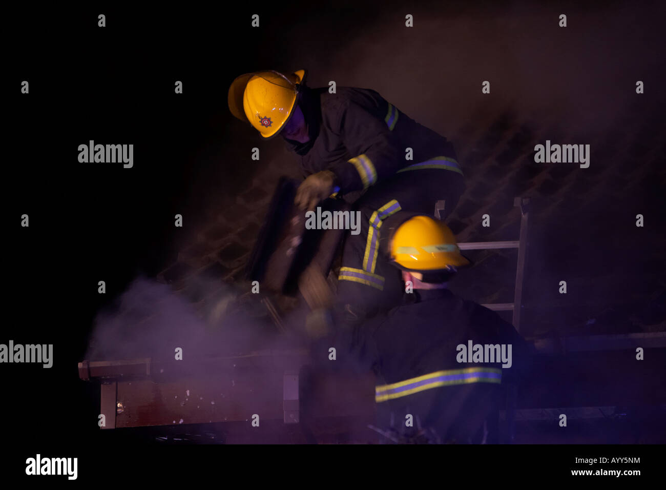 firefighters removing roof tiles from the roof of a burning house to get access to the fire below - Stock Image