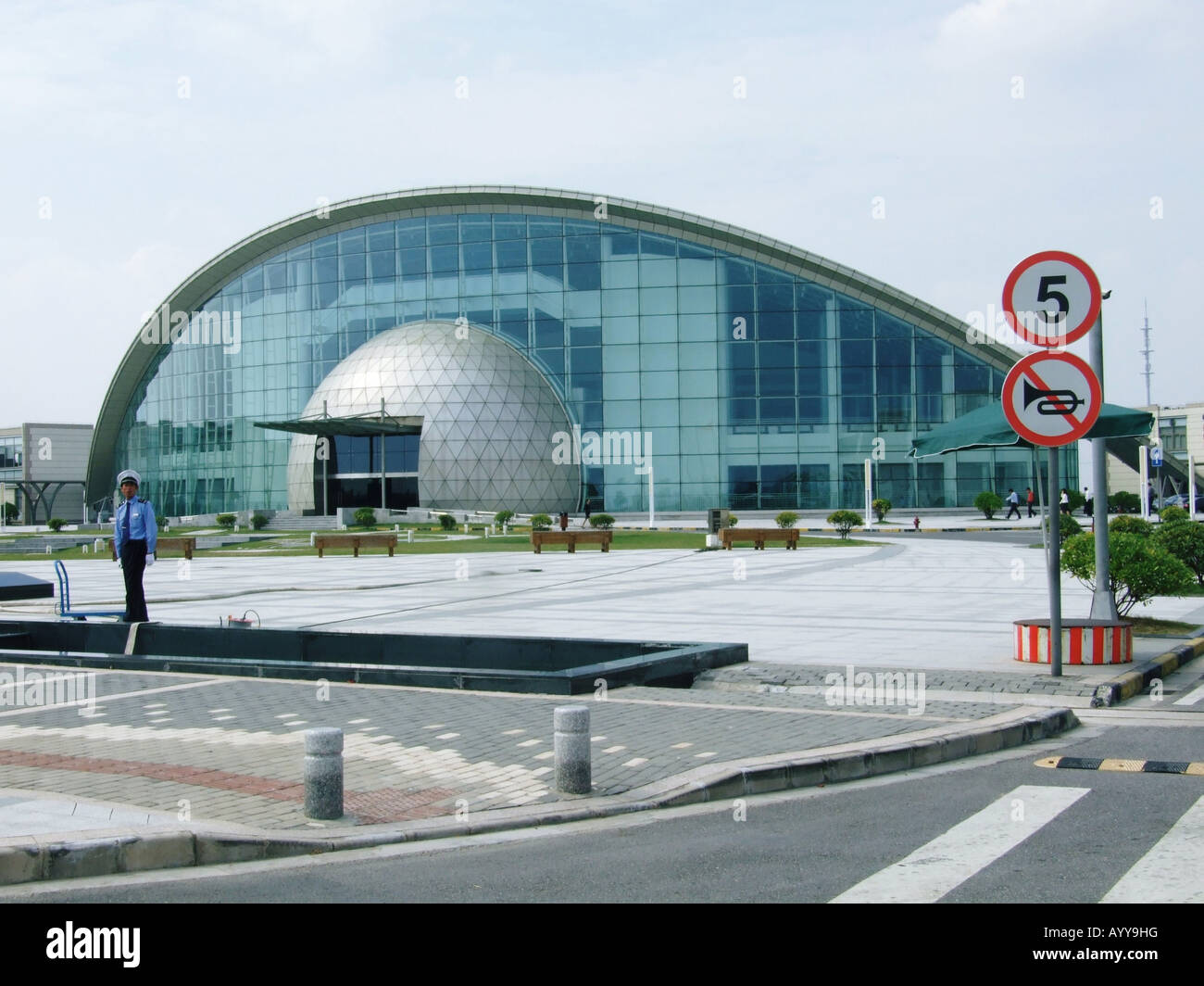 A security guard stands in front of the Exhibition Center of Shanghai in Lingang New City near Shanghai China Stock Photo