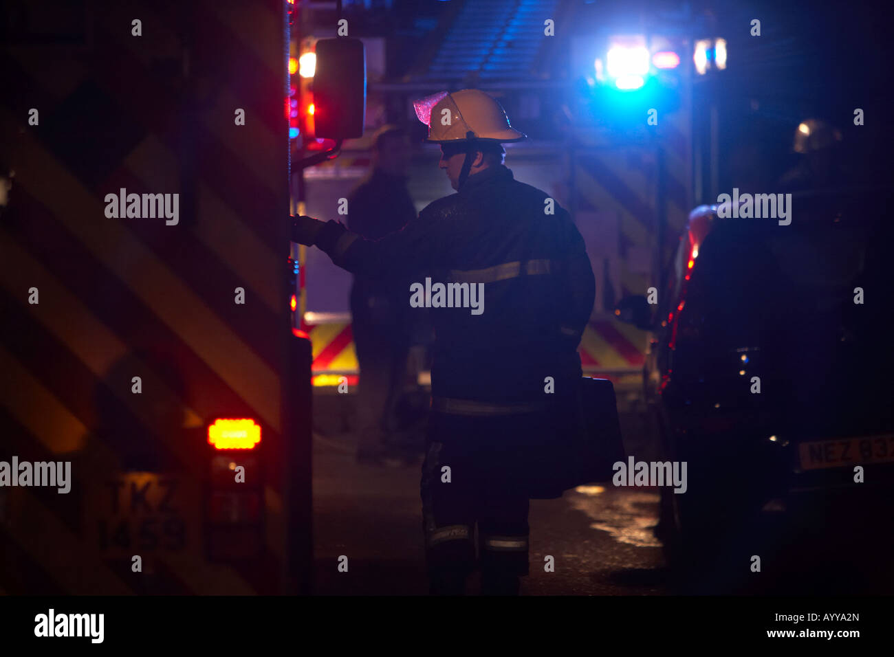 firefighter wearing a helmet and protective overall carrying a case opens door of a fire engine on a street at night - Stock Image