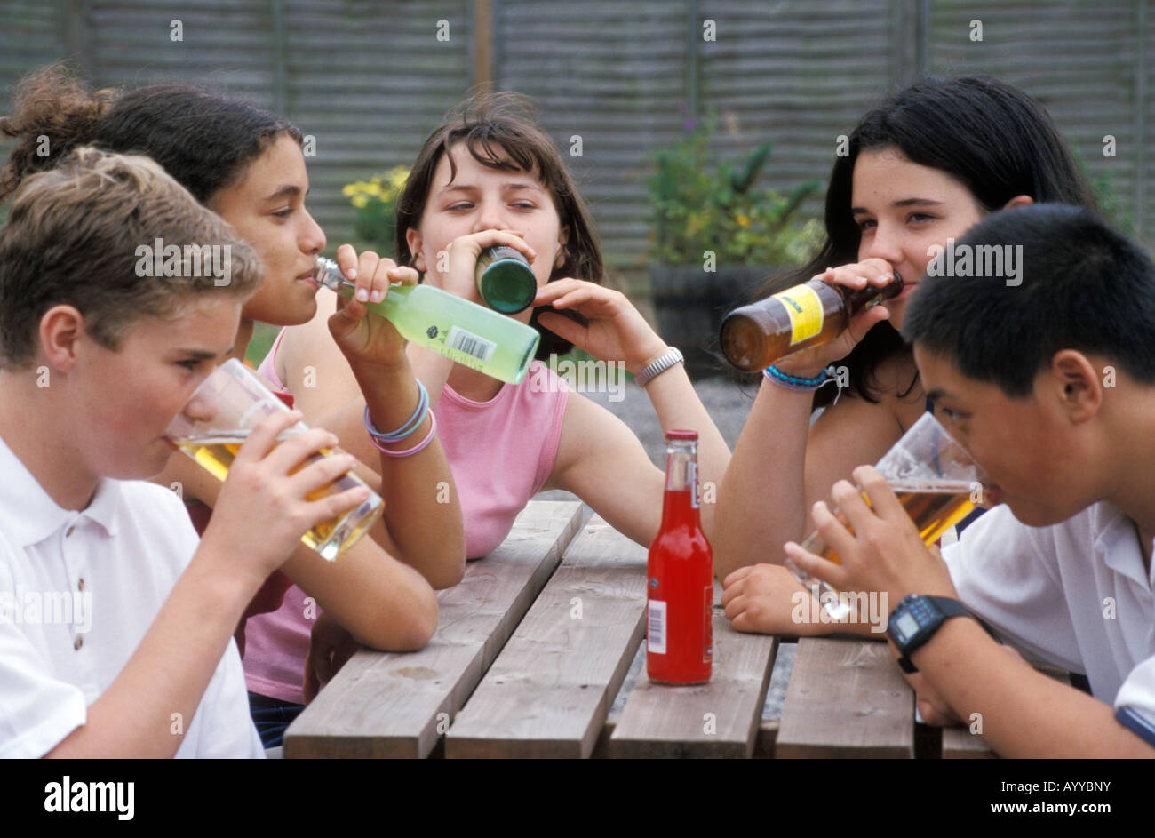 teenage boys and girls at garden table drinking alcohol - Stock Image