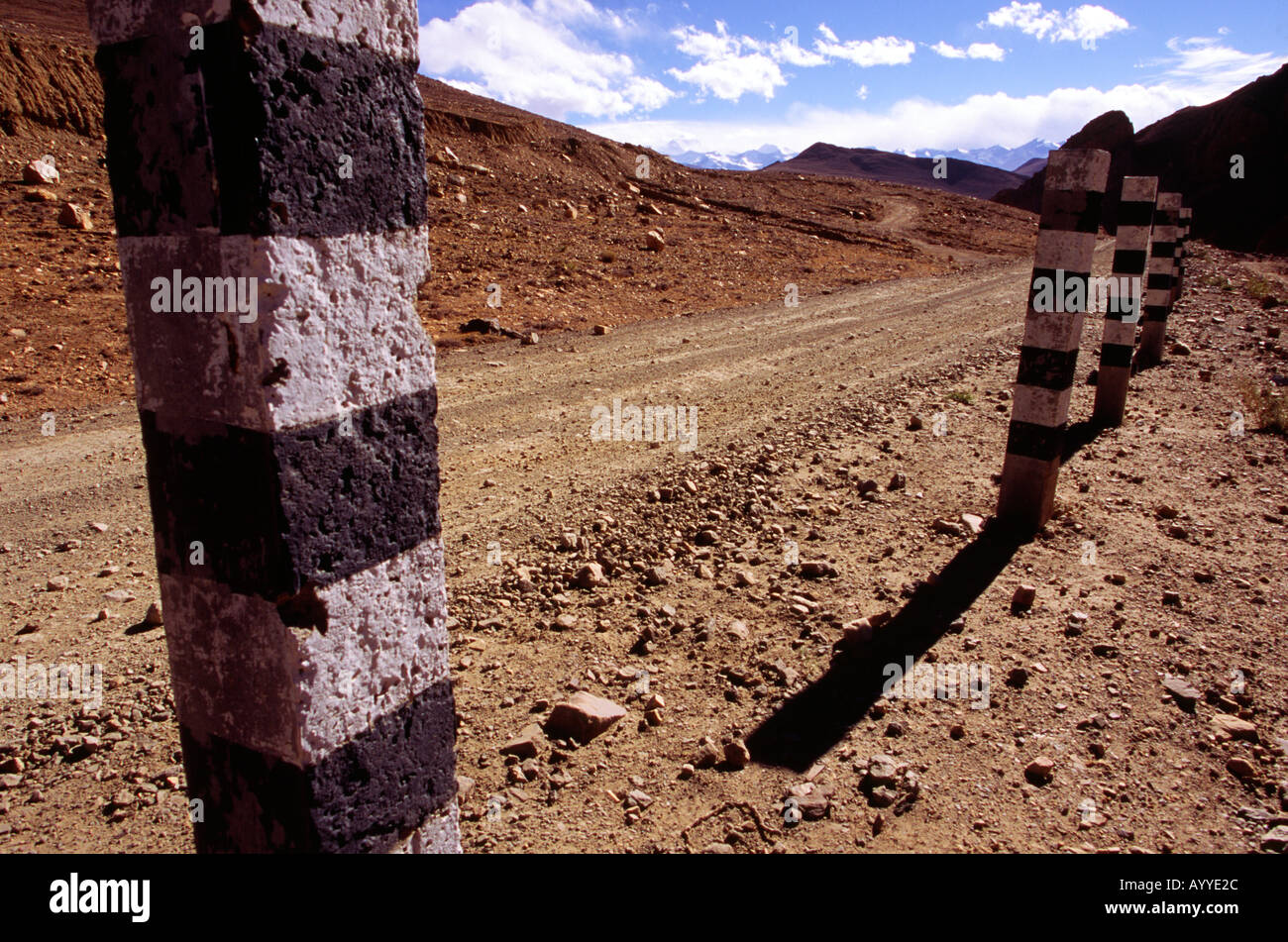 Striped painted road side contrite posts on a dusty gravel offroad highway in the Himalayas Tibet China Asia - Stock Image
