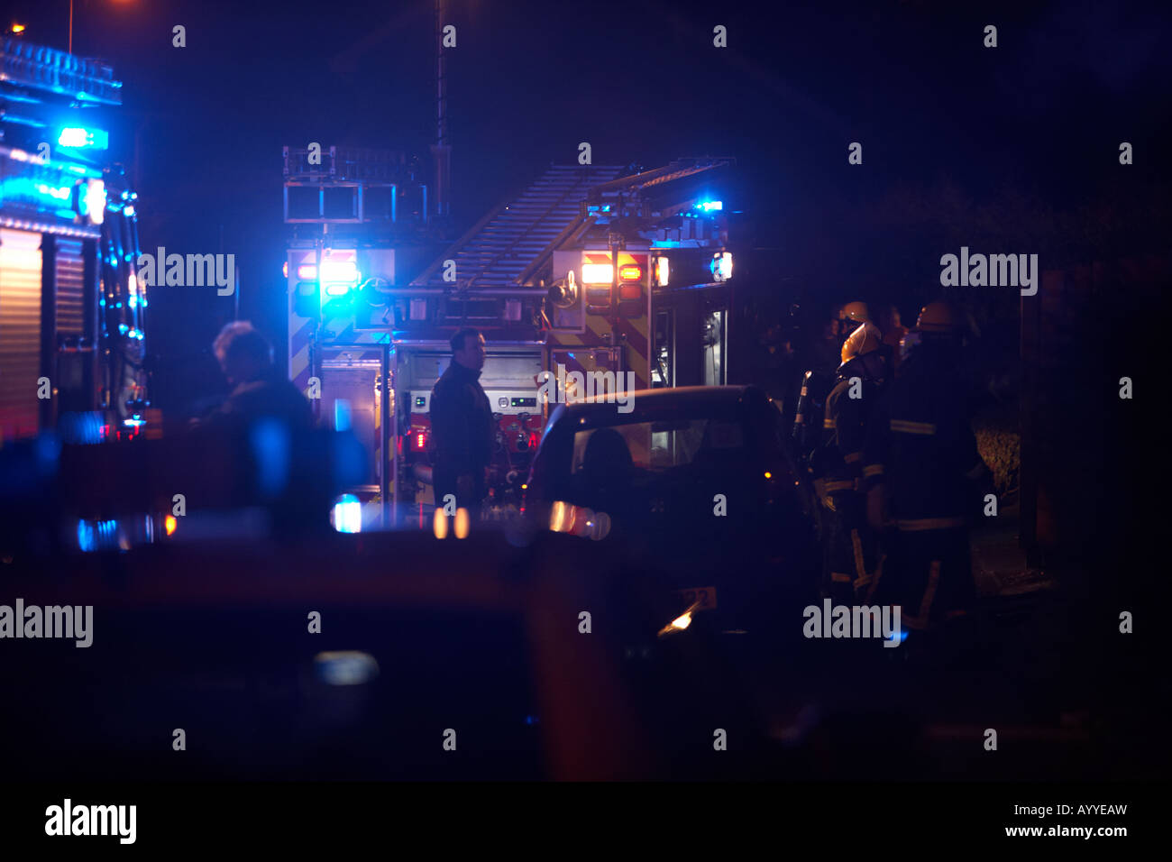 firefighters waiting behind a fire truck pumping engine through parked cars at the scene of a house fire in the - Stock Image