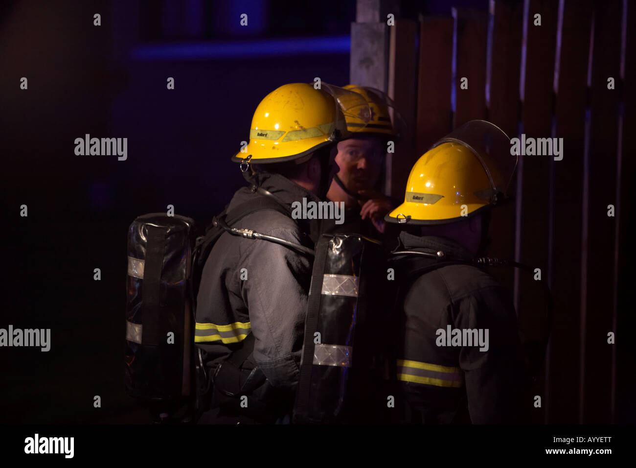 firefighters wearing helmets protective clothing and breathing apparatus waiting to gain entry to a residential - Stock Image