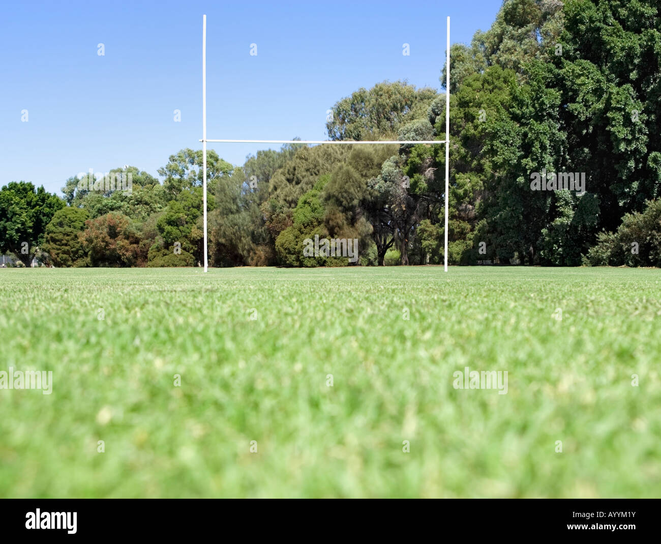 Looking up towards rugby posts in a sports field from grass level. - Stock Image
