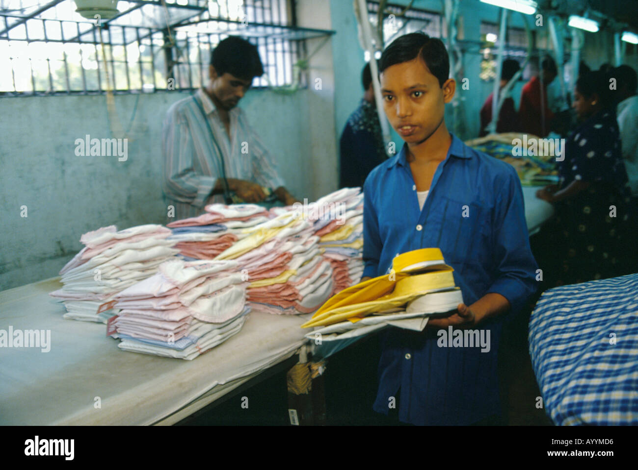 boy working in a garment factory in the capital Dhaka, Bangladesh - Stock Image