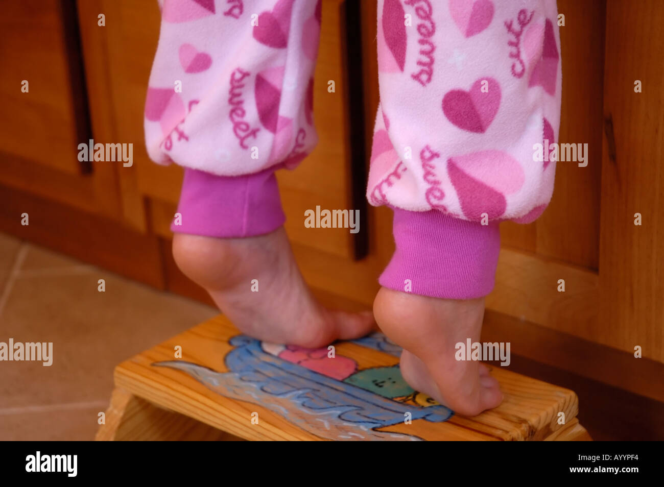 Young girl's feet on tiptoes on a bathroom stool. - Stock Image