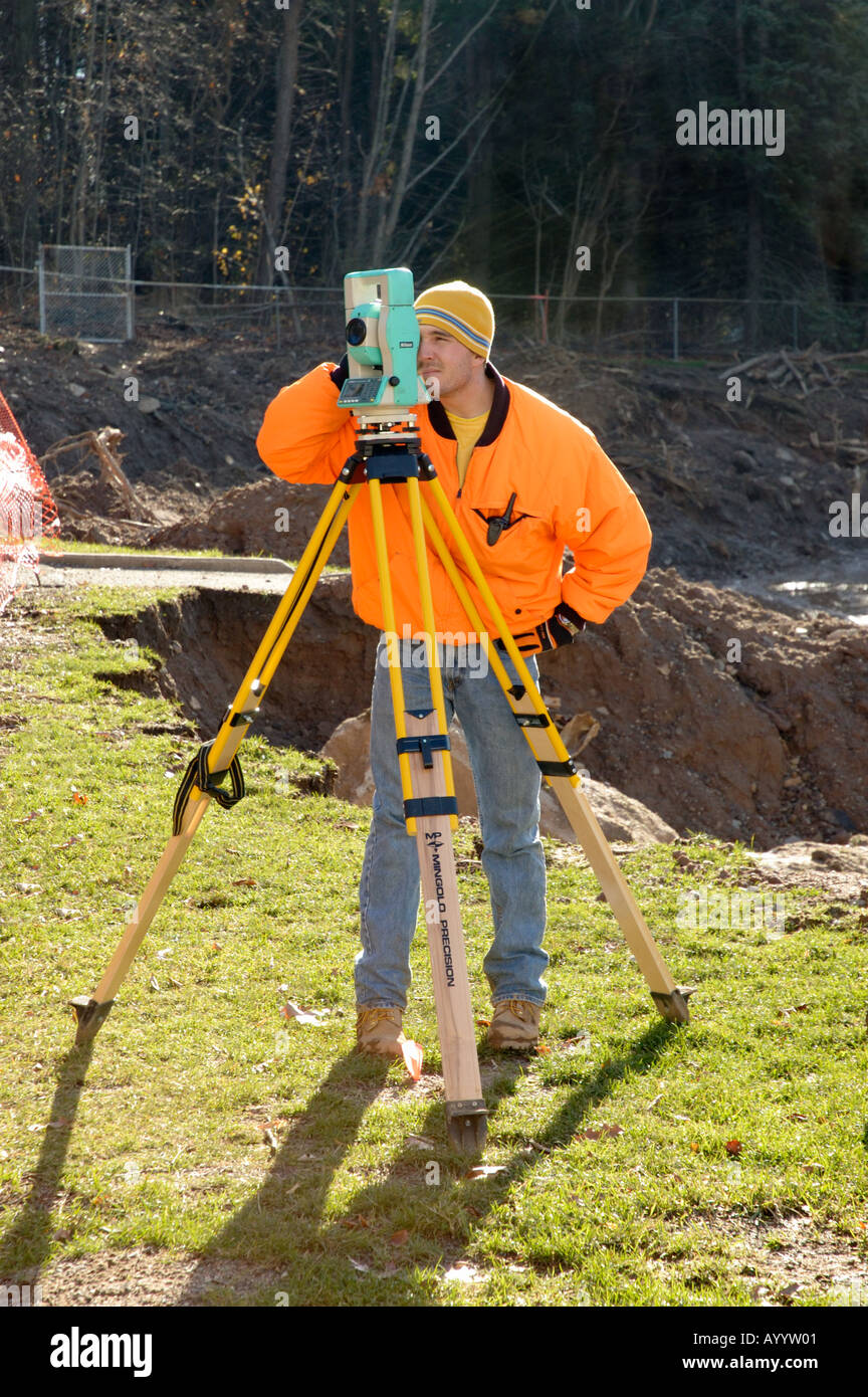Surveyor at construction site making measurements - Stock Image