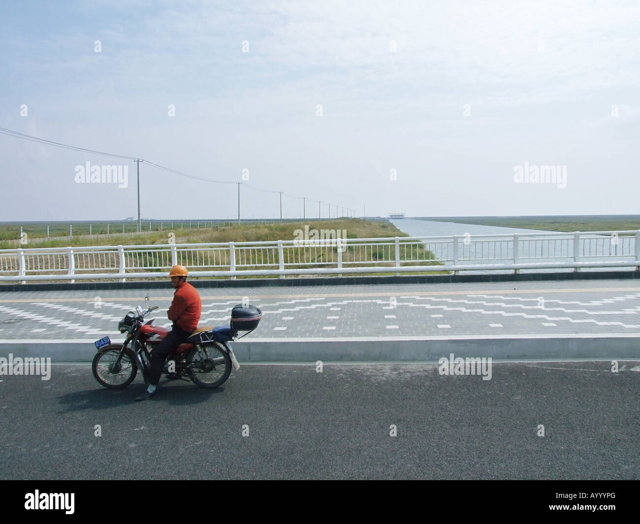 A man on a motorcicle in front of the channel connecting Water Drop Lake with the sea Lingang New Town near Shanghai Stock Photo