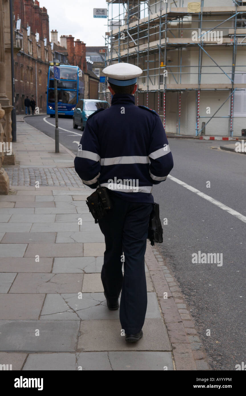 Traffic warden walking down street looking for offending vehicles - Downing Street Stock Photo