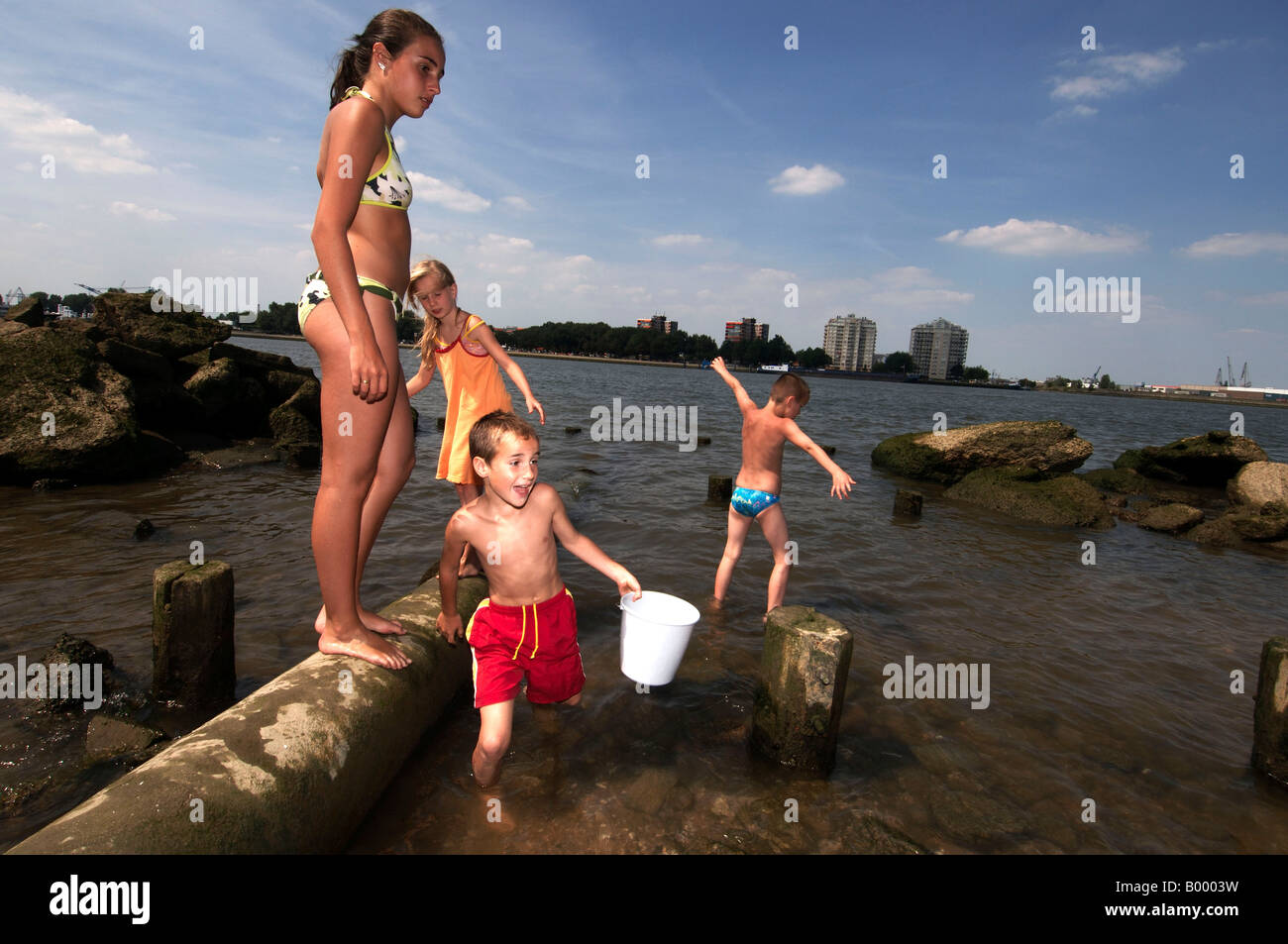 Port of Rotterdam Heyplaat summertime children swimming close to a waste pipe in the new meuse - Stock Image