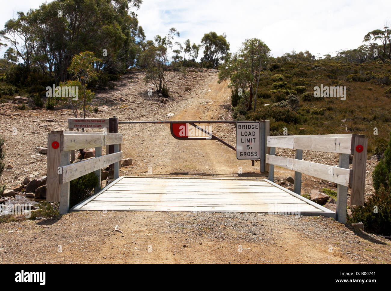 A closed gate leading to a track in the Tasmania high country during summer. - Stock Image