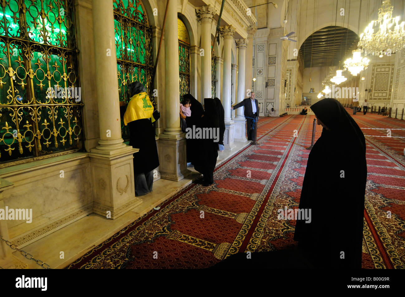 Women, including one with a Hezbollah flag, praying at the shrine of John the Baptist in the Umayyad mosque in Damascus, - Stock Image