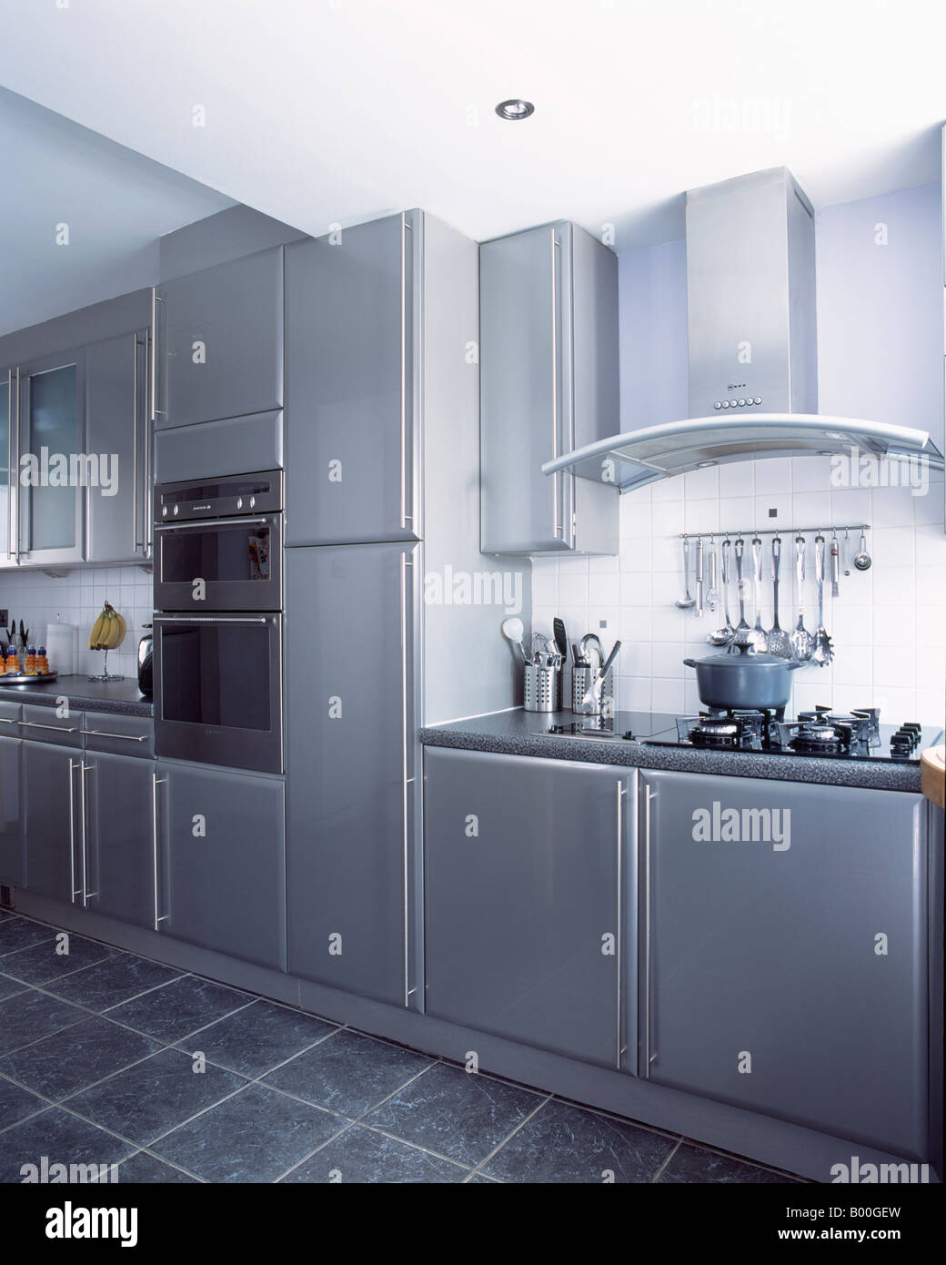 Wall mounted ovens in modern metallic grey kitchen with slate floor ...
