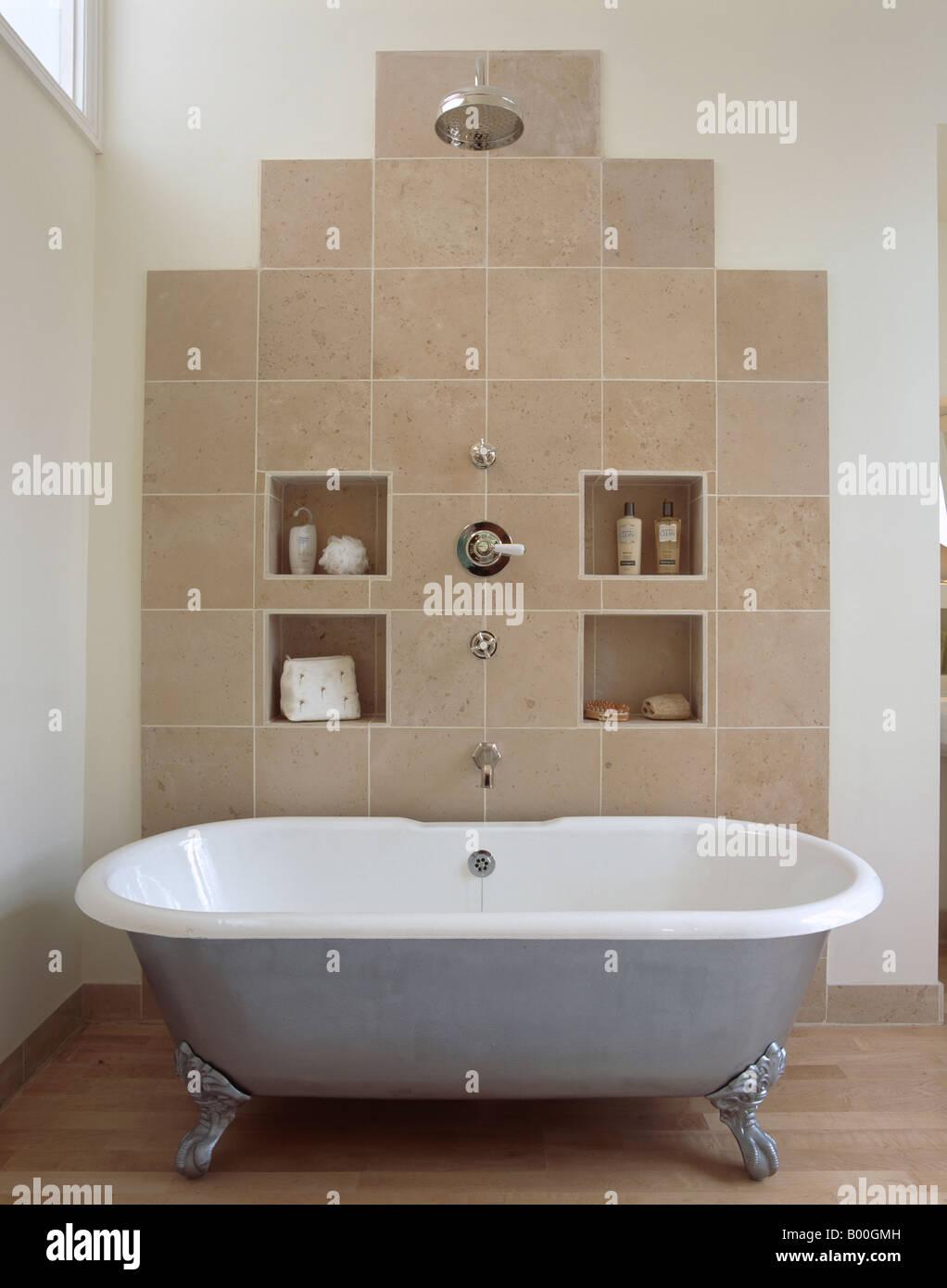 Large Chrome Showerhead Above Metallic Clawfoot Bath In Modern Bathroom  With Alcove Storage On Beige Tiled Wall