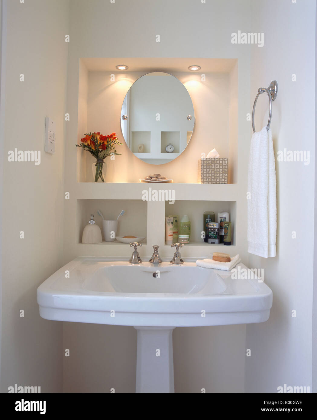 Downlighting Above Oval Mirror In Alcove Above White Pedestal Basin In  Modern Bathroom