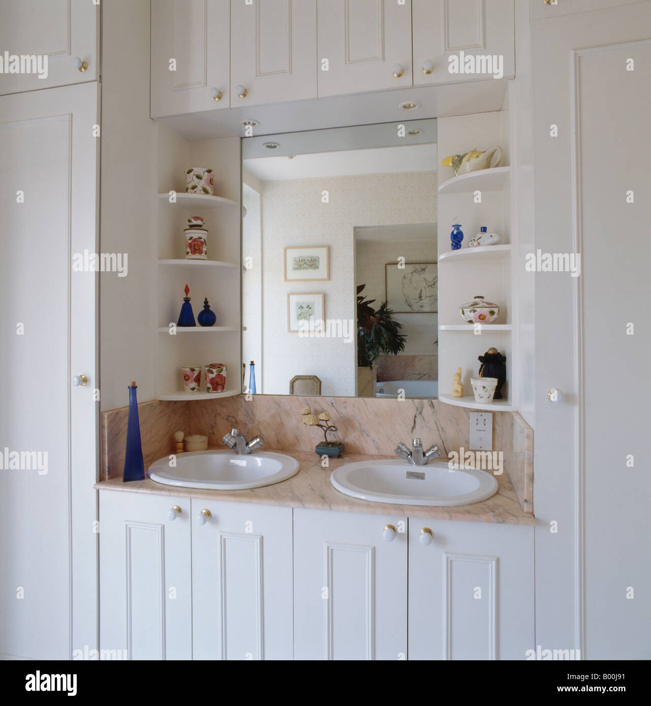 shelves on either side of mirror above double basins in white vanity rh alamy com