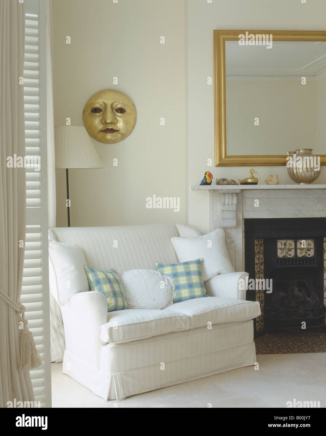 Charmant White And Checked Cushions On Small White Sofa Beside Fireplace In White  Living Room With Gilt Sun Sculpture On Wall