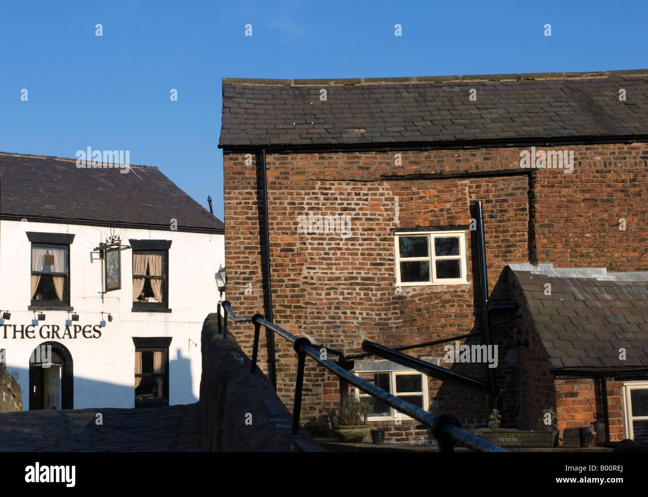 The Grapes pub at Croston in Lancashire from the old packhorse bridge over the River Yarrow - Stock Image