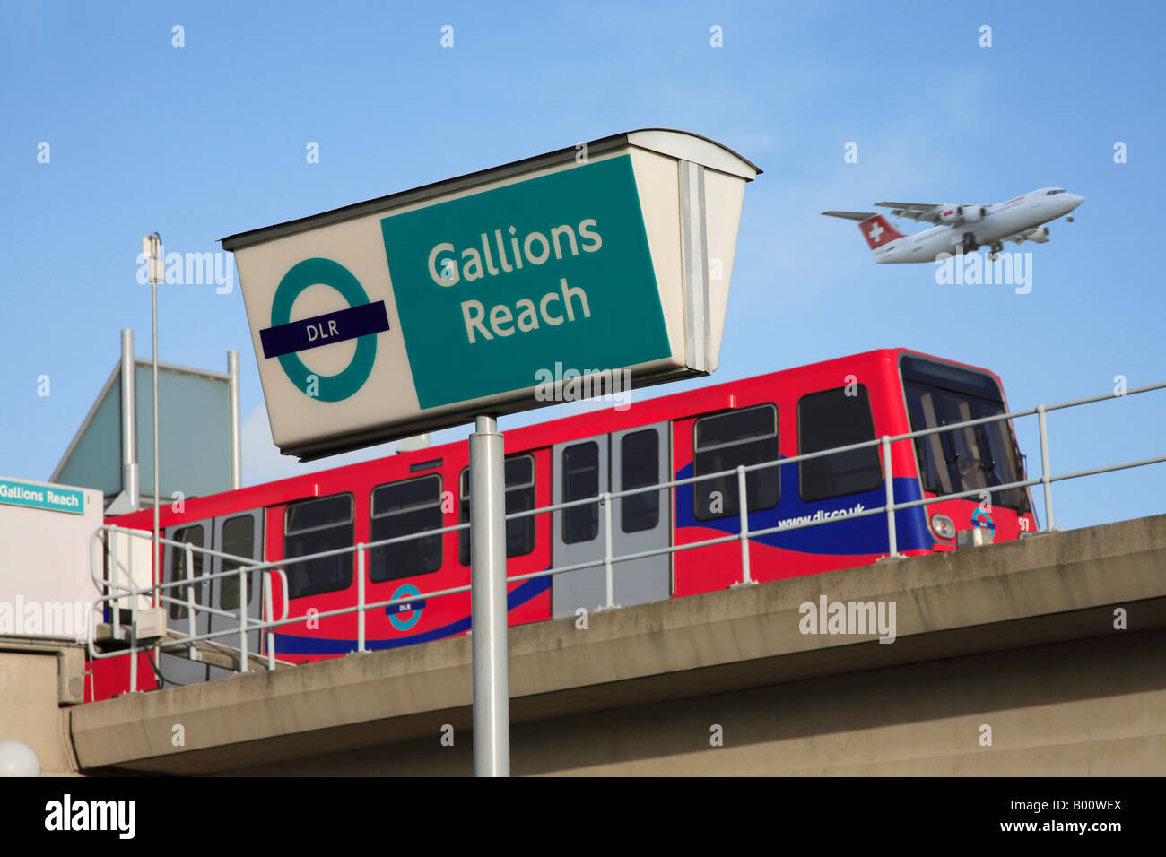 Docklands Light Railway Train at Gallions Reach Station with Swissair Plane Overhead. Stock Photo