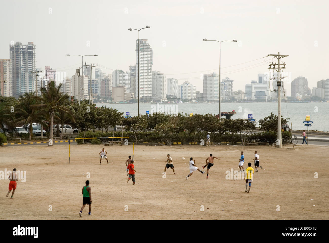 Young men playing football on the waterfront with Bocagrande behind Cartagena de Indias Colombia - Stock Image
