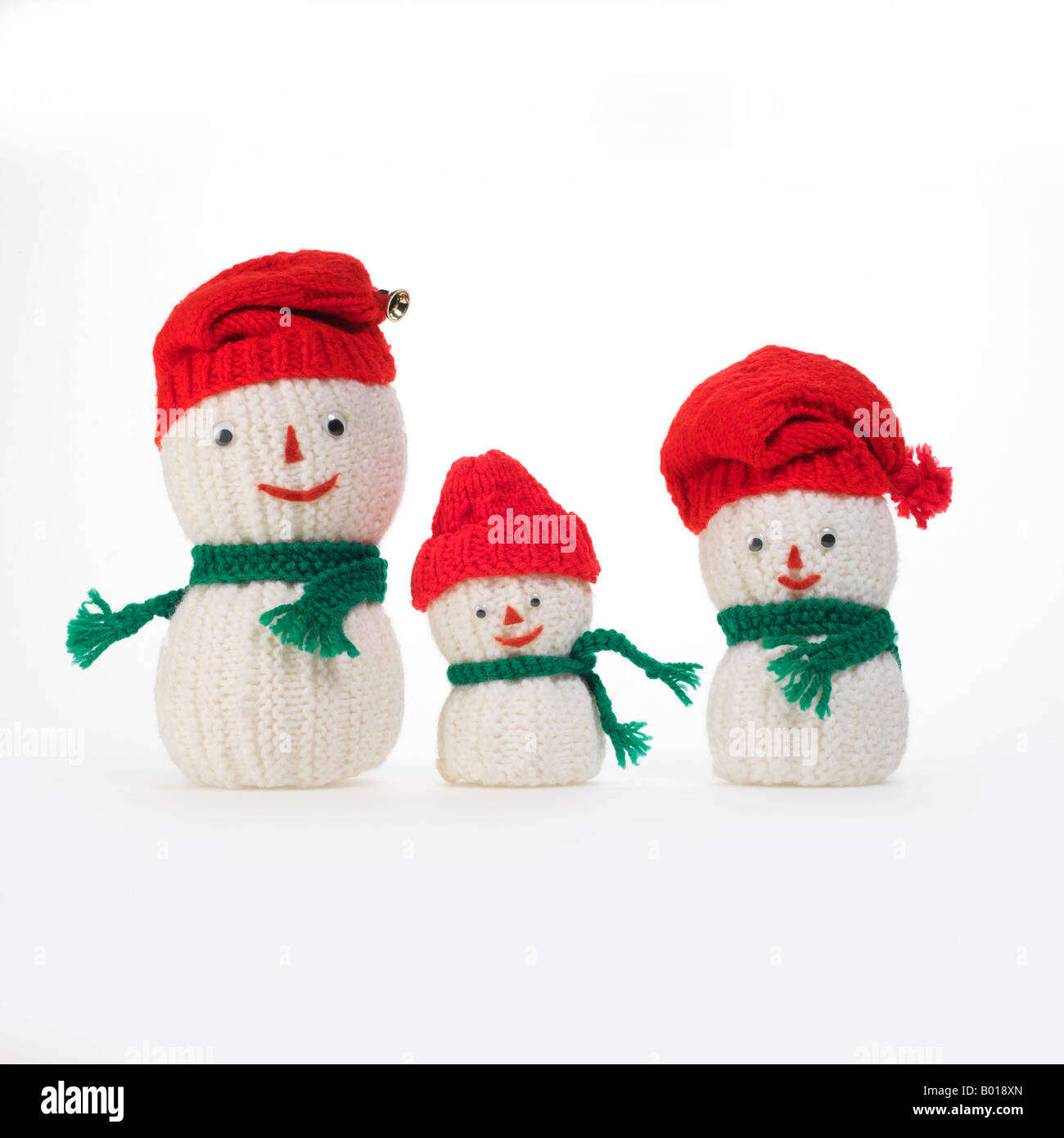 3 knit snowmen family with red caps and green scarves - Stock Image