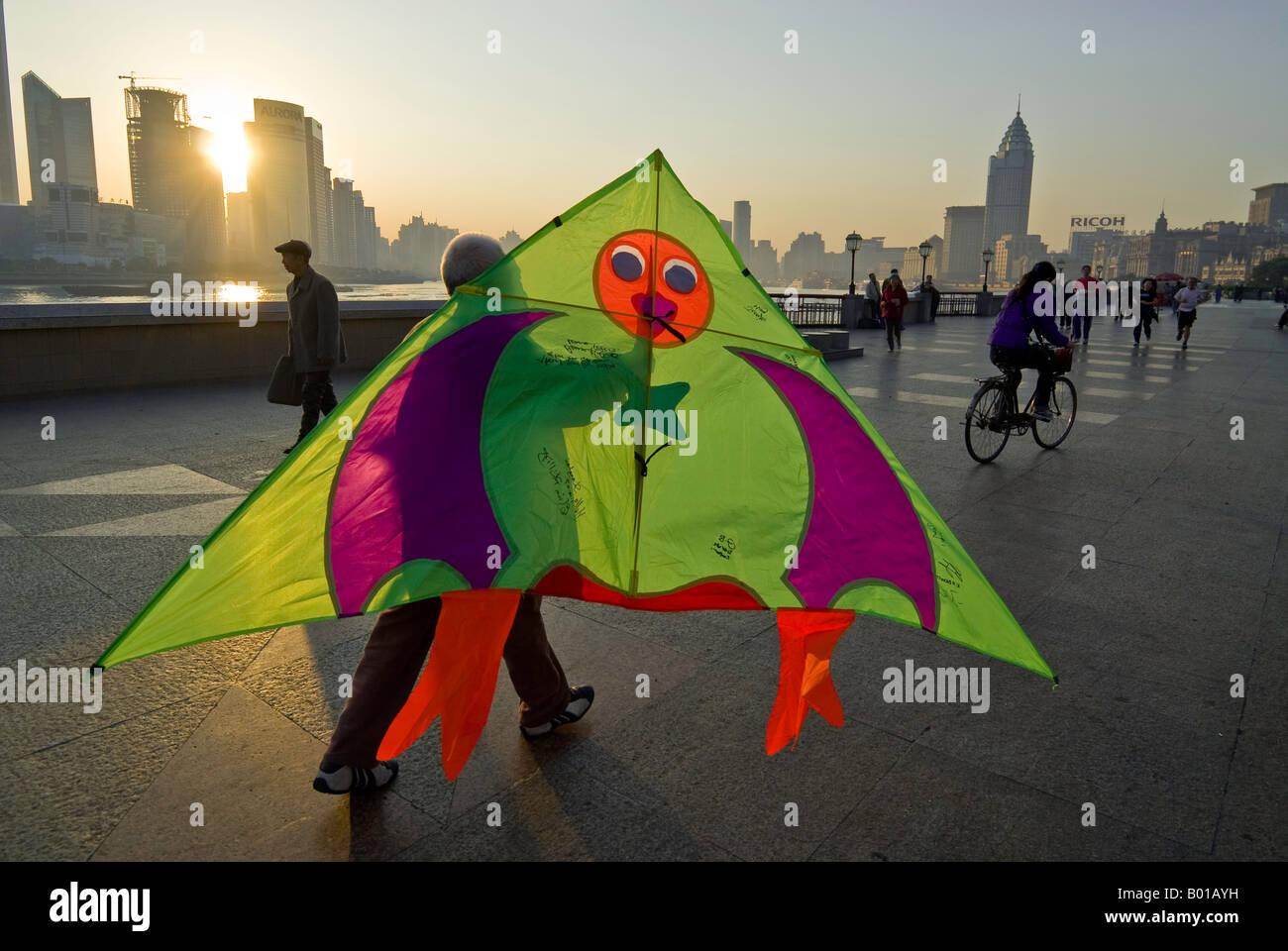 Sunrises over skyline as man prepares to fly kite, The Bund, Shanghai, China - Stock Image