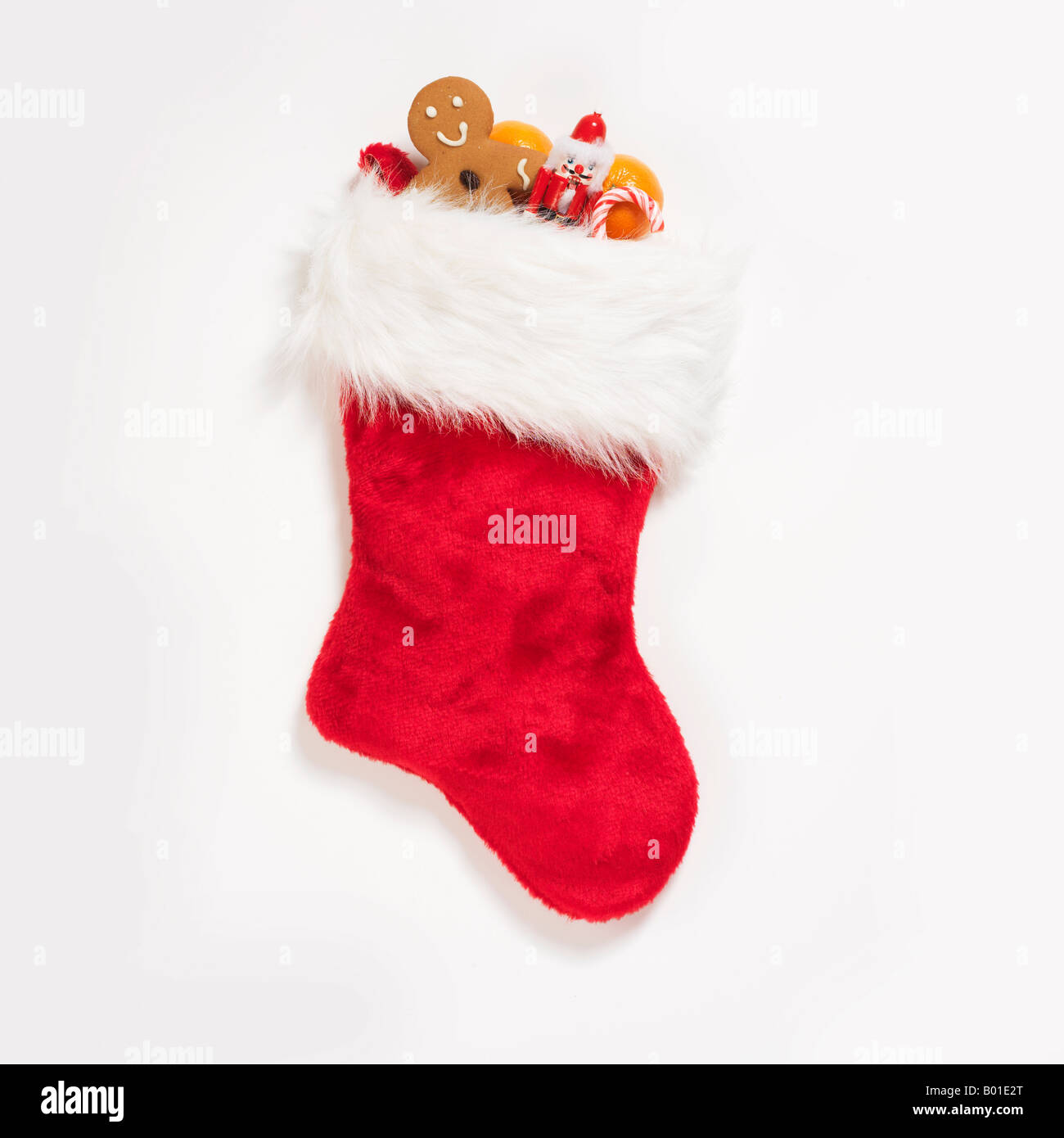 Christmas stocking stuffed with assorted treats and sweets on white background - Stock Image