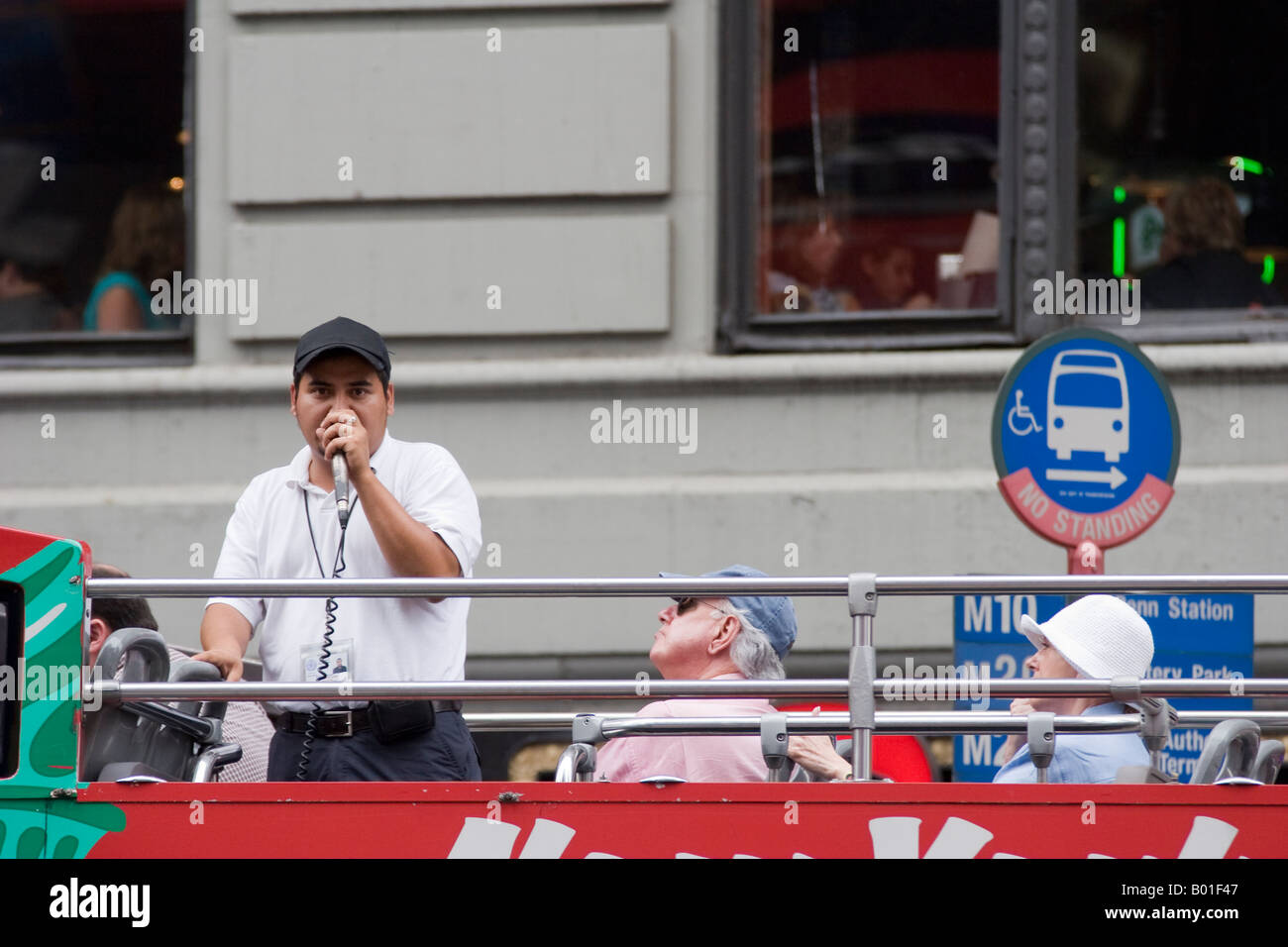A tour guide on a bus speaks into a microphone in New York City, New York, USA, August, 2006 - Stock Image