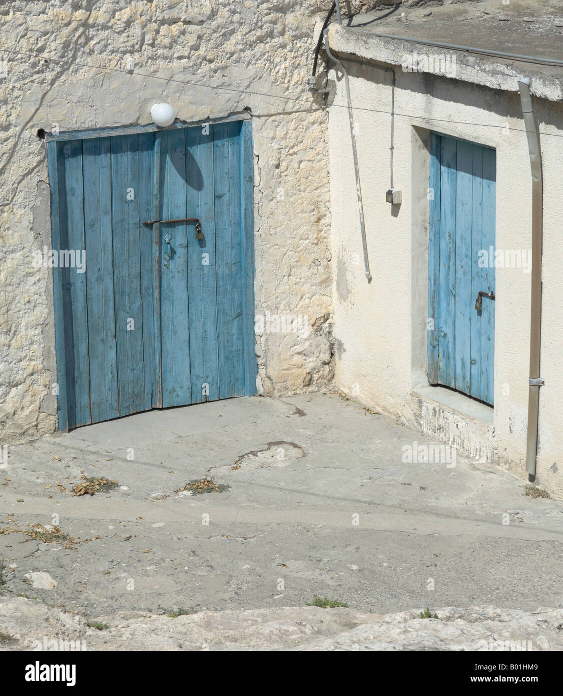 Two blue doors in a quiet courtyard in the traditional Greek Cypriot village of Peristerona near Polis Paphos Region Cyprus & Two blue doors in a quiet courtyard in the traditional Greek Cypriot ...