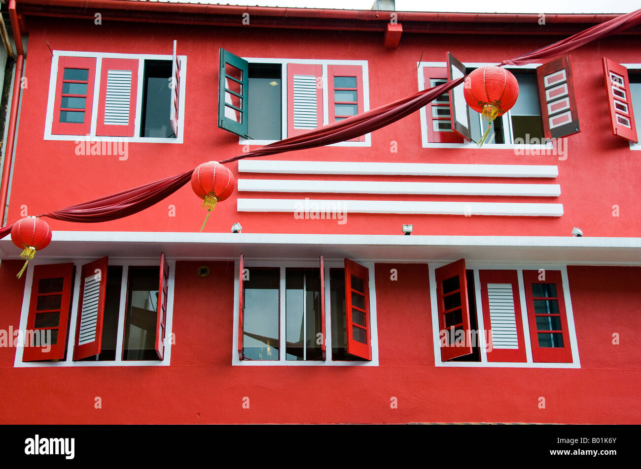 windows with shutters on second story apartment in Singapore - Stock Image