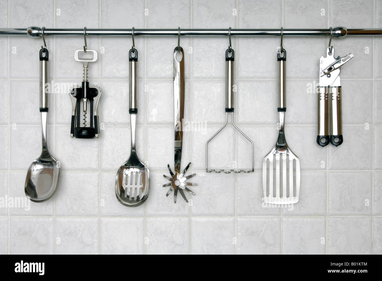 Stainless steel kitchen utensils hanging on a rack, against white ...