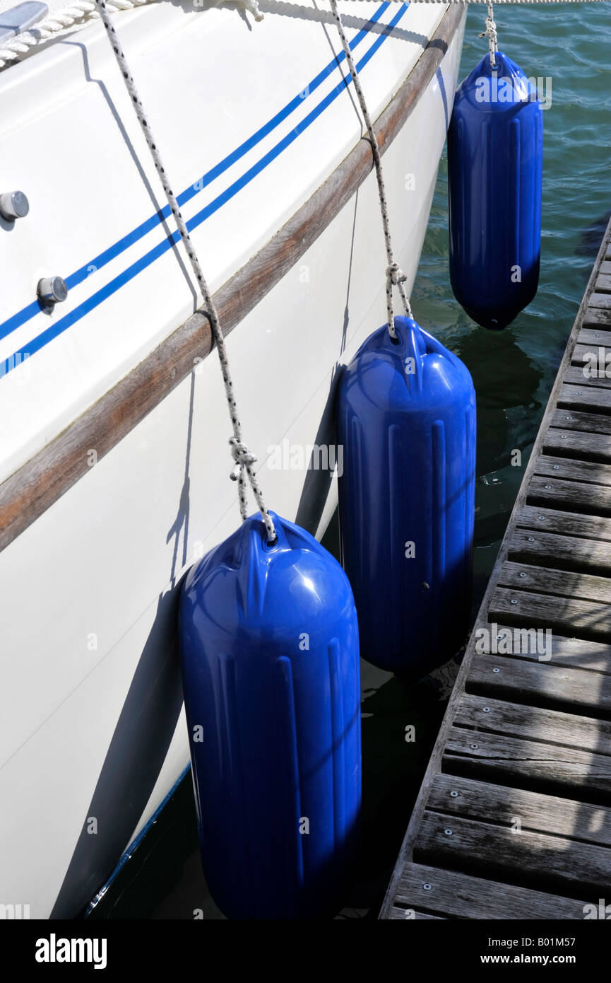 blue fenders hanging from the side of a moored sailing boat - Stock Image