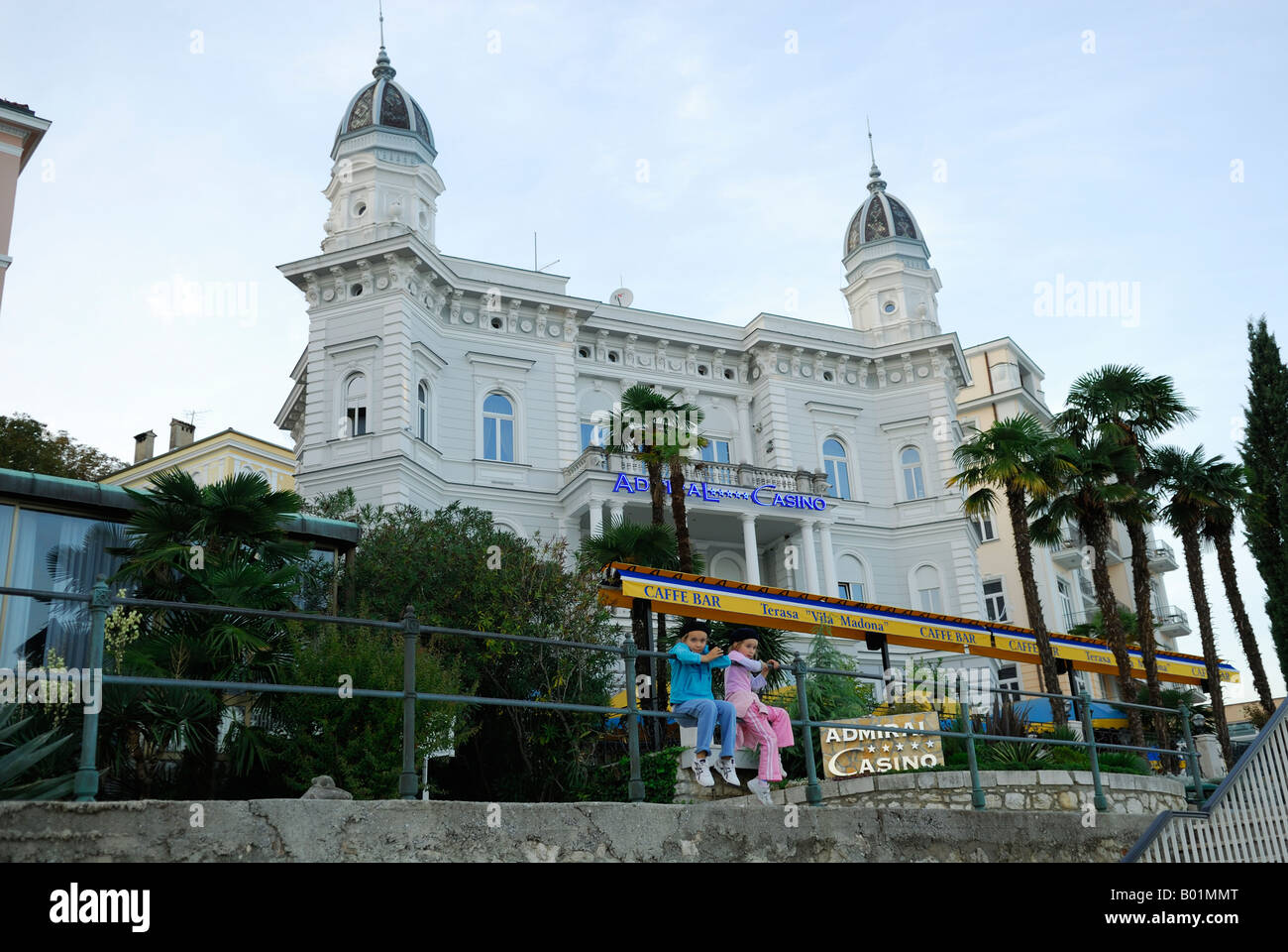 2 children wearing French berets, sitting on railing, Admiral Casino building in background. Opatija, Croatia Stock Photo