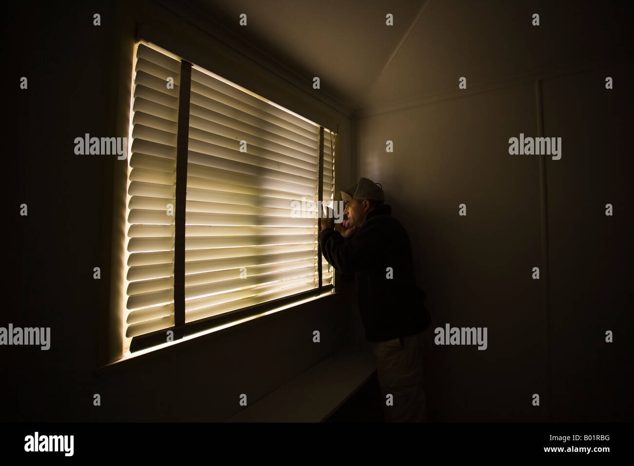 Man forties looks out window through slats of venetian blind - Stock Image